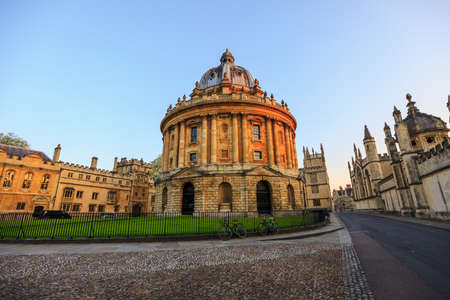 The Radcliffe Camera in Oxford at sunrise with no people around, early in the morning on a clear day with blue sky. Oxford, England, UK.