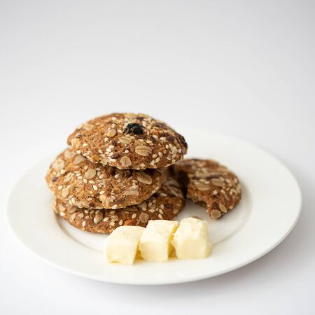 oatmeal cookies with seeds and butter on a white plate