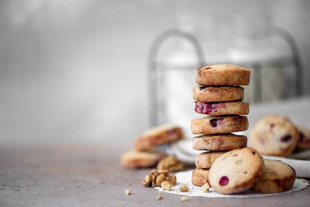 friable round cookies with cranberries stacked on a table