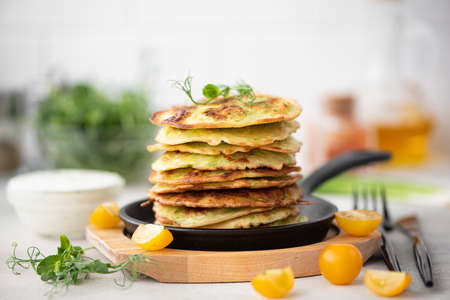 small zucchini fritters with herbs and sour cream sauce in a black skillet Foto de archivo