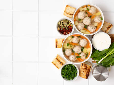 potato soup with meatballs, carrots and herbs in bowl