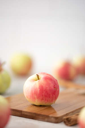 yellow red small apple with a handle on a wooden board