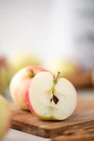 small ripe apple cut in half on wooden board