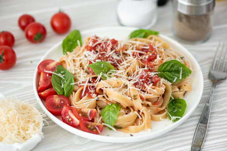 fettuccine with tomato sauce, parmesan and basil on white plate