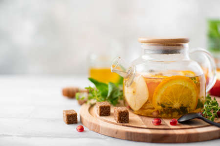 fruit tea with orange and apple in a glass teapot 免版税图像
