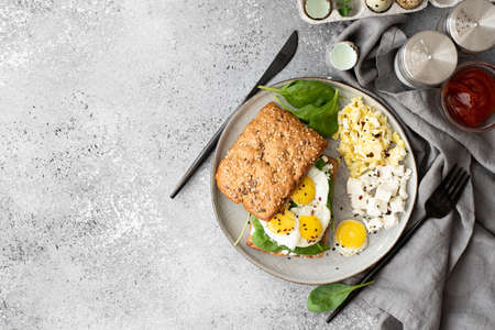 sandwich with quail eggs, curd cheese and spinach, top view