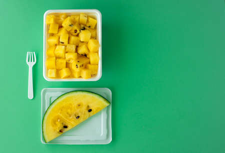 ripe yellow watermelon cut into pieces in a plastic white bowl 版權商用圖片