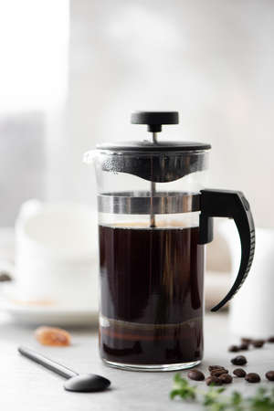 hot black coffee in a glass coffee pot with small white cups