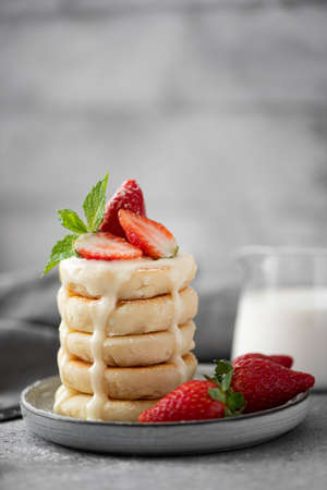 cottage cheese pancakes with fresh strawberries, mint and milk on a gray plate 写真素材