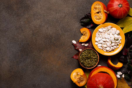 small orange pumpkins and pumpkin seeds on a dark table, top view