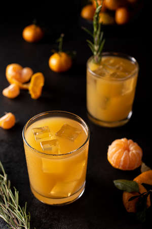 freshly squeezed tangerine juice with ice in a glass on a dark background