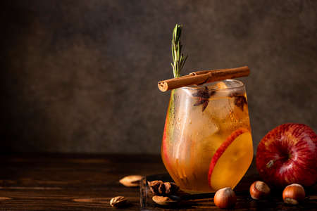homemade apple cider with apple pieces, cinnamon and spices in a glass