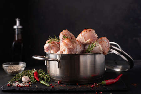 raw chicken drumsticks with spices and soy sauce in a saucepan, close-up Archivio Fotografico