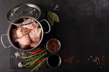 Raw chicken drumsticks with spices and herbs in a gray saucepan Stok Fotoğraf
