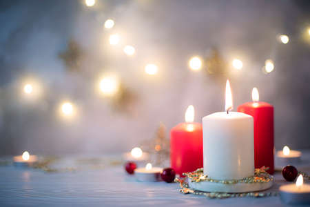 three burning candles and christmas garland on a blue background, close-up