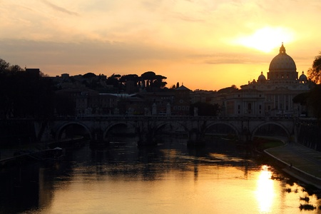 A sunset over Saint Peters Cathedral in Vatican City photo