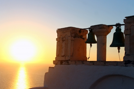 Bells lighted by the sunset on Santorini island photo