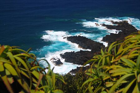 The intense blue sea and the black volcanic rocks