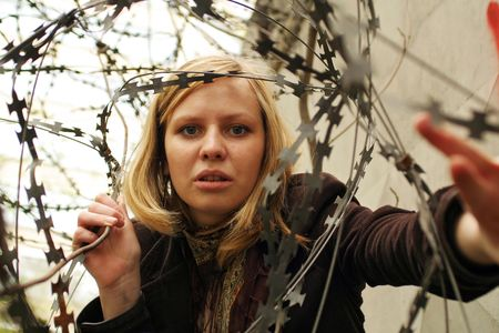 Beautiful girl looking through barbed wire Stock Photo - 968584