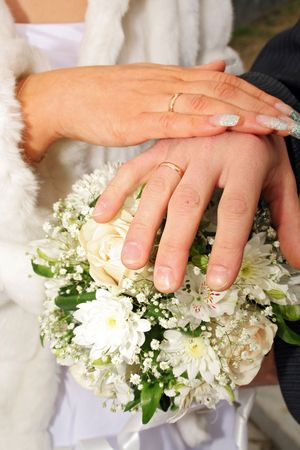 newlyweds hands with gold rings on fingers above flowers Stock Photo - 1126498