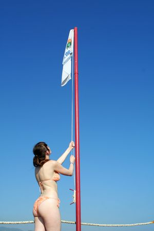 flagstaff: Girl lifting flag up on flagstaff isolated on blue sky Stock Photo