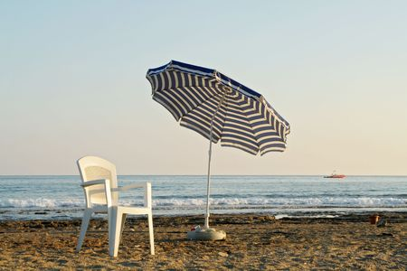 pending: chair and umbrella on sand beach near by sea Stock Photo