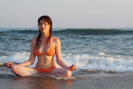 effortless: effortless yoga posed girl sitting on sea coast