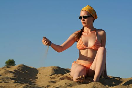falling out: sad woman in swimwear pouring sand down