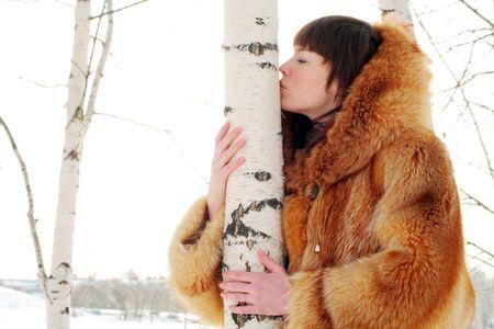 fur hood: Woman in red fur coat kissing birch trunk Stock Photo
