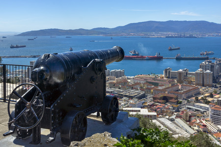 barrel bomb: vintage gun on a metal carriage on the background of the commercial port. Reserve Upper Rock. Gibraltar
