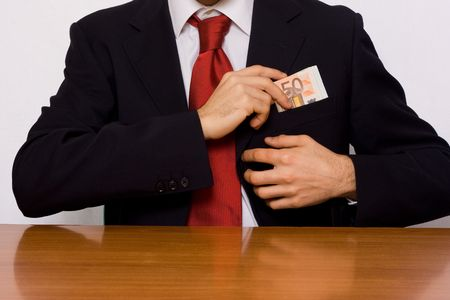 breast pocket: businessman putting money on his breast pocket