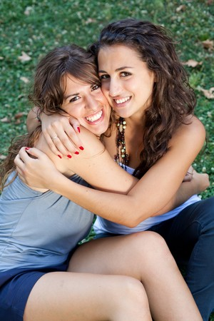 two girls hugging: two girls hugging themselves tightly