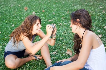 Chica en el parque toma fotos a su amigo femenina