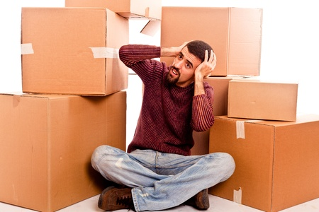 Stressed Young Man on Moving Swamped with Boxes photo