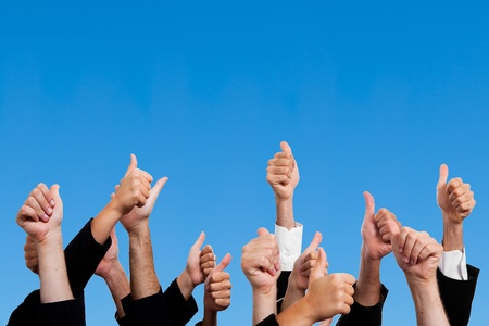 cheering: Multiracial Thumbs Up Against Blue Sky