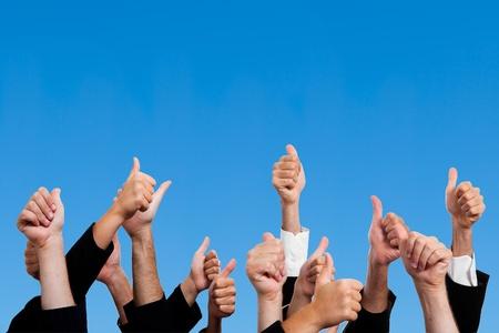 Multiraciale Thumbs Up tegen blauwe hemel