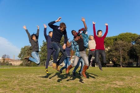 enjoyment: Group of Happy College Students Jumping at Park Stock Photo