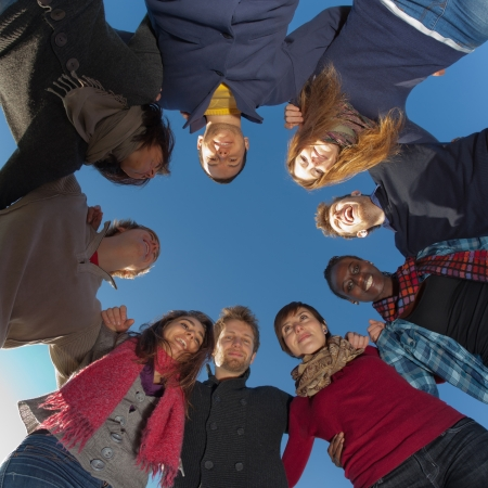 integrate: Multiracial People Holding Hands in a Circle, Low Angle View