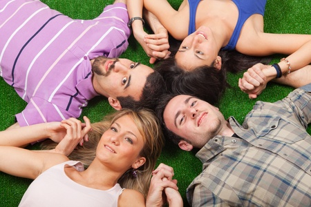 Young People Lying on Green Ground with Hands Joined Stock Photo - 9009778