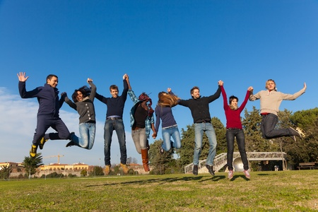 Group of Happy College Students Jumping at Park photo