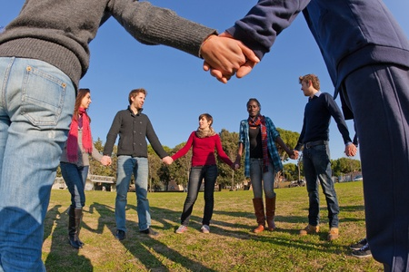 friendship circle: Multiracial Young People Holding Hands in a Circle Stock Photo