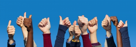 thumbs up woman: Multiracial Thumbs Up Against Blue Sky