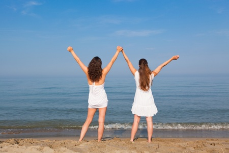 Two Young Women with Arms Outstretched on Seaside photo