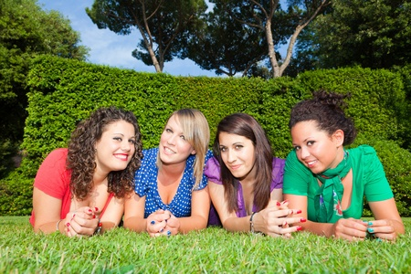 Teenage Female Friends Lying on Green at Park photo