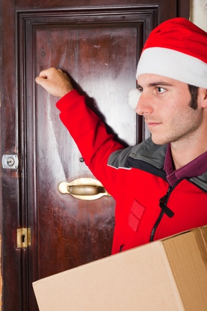Delivery Boy with Christmas Hat Knock at the Door photo