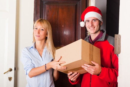 Delivery Boy with Christmas Hat and Box for Young Woman photo