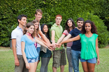 Happy Teenage Group with Hands on Stack photo