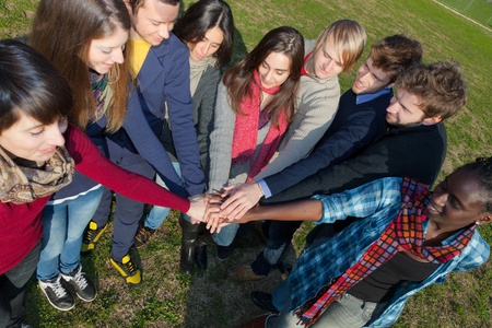 Happy College Students with Hands on Stack photo