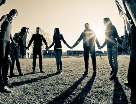 manos sosteniendo: Multirraciales jóvenes tomados de la mano en un círculo