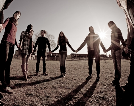 Multiracial Young People Holding Hands in a Circle photo
